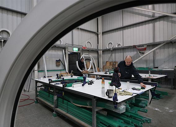 Staff in factory cutting window frames into shape